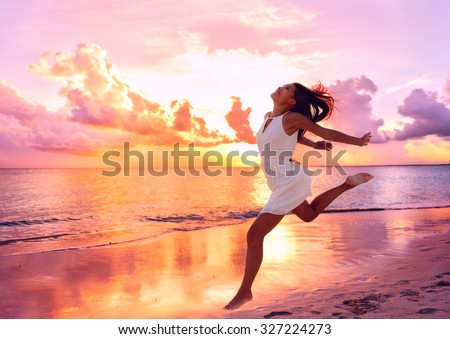 Happy beautiful free woman running on the beach at sunset jumping playful having fun in serene picturesque sunset at the ocean . Aspirational happy lifestyle with pretty young lady enjoying freedom. - stock photo