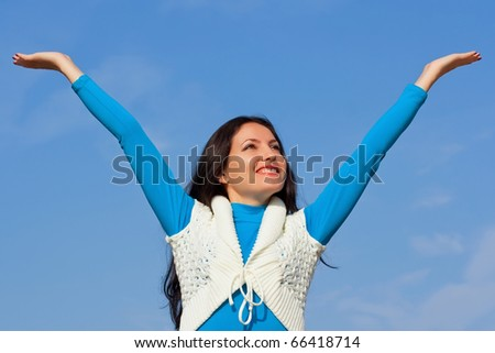 Happy beautiful girl against the blue sky - stock photo