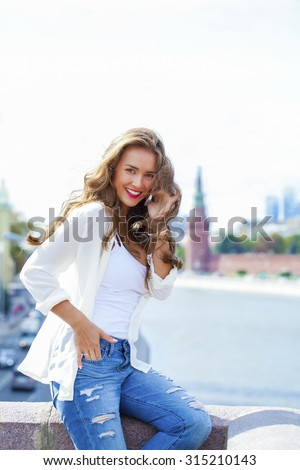 Happy beautiful girl calling by phone in a summer street - stock photo