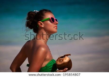 Happy beautiful girl in green bikini at caribbean beach with coconut cocktail. Happy carefree freedom girl in summer day.  - stock photo