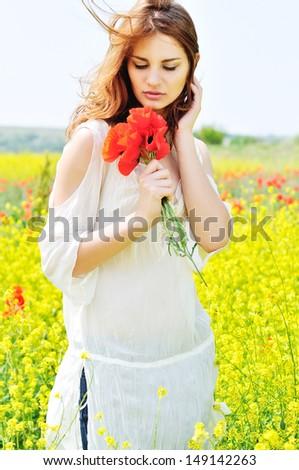 happy beautiful girl in rapeseed field in bloom - stock photo