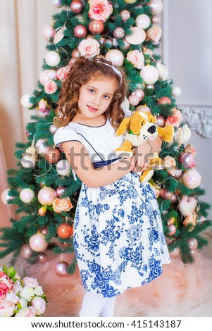 Happy beautiful girl Princess  is hugging soft toy on background of the Christmas tree. Happy New Year little Princess - stock photo