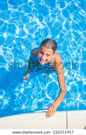Happy beautiful girl relaxing in the pool. Vertical view - stock photo