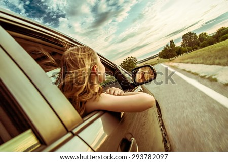 Happy beautiful girl traveling in a car across Europe with focus in front of the car - stock photo