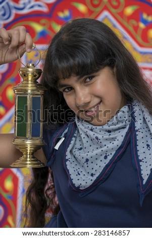 Happy Beautiful Girl with Lantern Celebrating Ramadan over Ramadan Fabric - stock photo