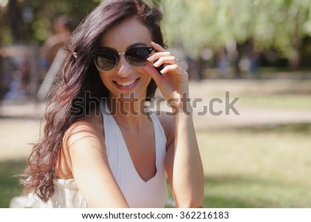 Happy beautiful girl with long dark hair and derk glasses sitting in the green park with green grass and trees on a sunny summer day in white shirt and denim shorts and keep her glasses - stock photo