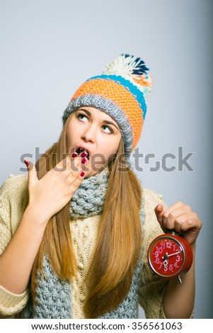 Happy beautiful girl yawns with alarm, knit cap, winter concept, photo studio, portrait of a woman isolated on gray background - stock photo