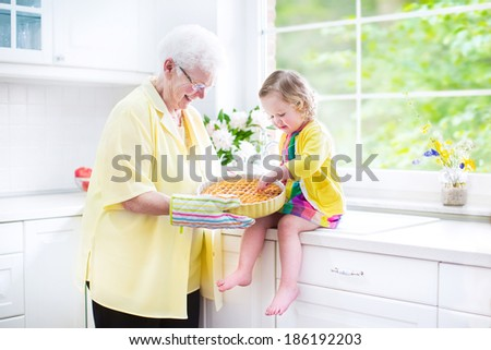 Happy beautiful great grandmother and her adorable granddaughter, curly toddler girl in colorful dress, baking an apple pie together standing next to white oven in sunny modern kitchen with big window - stock photo