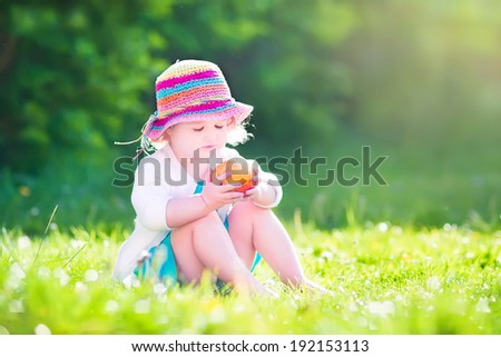 Happy beautiful little girl wearing a blue dress and colorful straw hat eating a big fresh apple as healthy snack sitting on a lawn playing in a sunny summer garden - stock photo