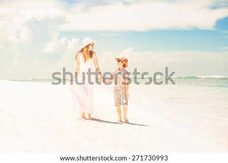 Happy beautiful mother and son walking along the beach in a sunny day - stock photo