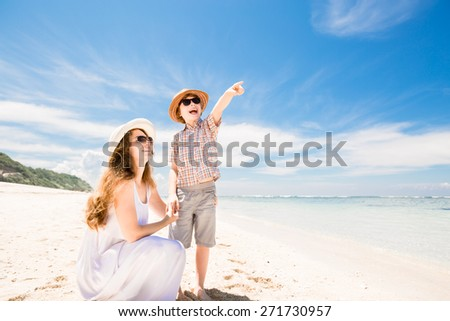 Happy beautiful mother and son walking along the beach in a sunny day with deep blue sky over the ocean on background - stock photo