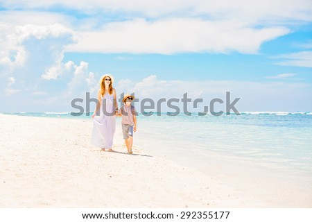 Happy beautiful mother in long white dress enjoying holidays on the beach with her young son wearing hat and sunglasses - stock photo
