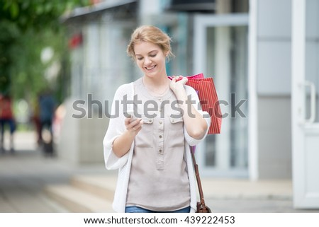 Happy beautiful person looking at phone while carrying shopping bags with purchases. Young joyful model reading message, texting, dialing number, using app on smartphone during shopping time. Portrait - stock photo