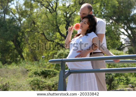 Happy beautiful pregnant woman and her husband - stock photo