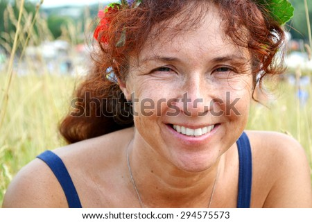 Happy beautiful redhead woman with flowers in her hair in her fourties smilling outdoors - stock photo