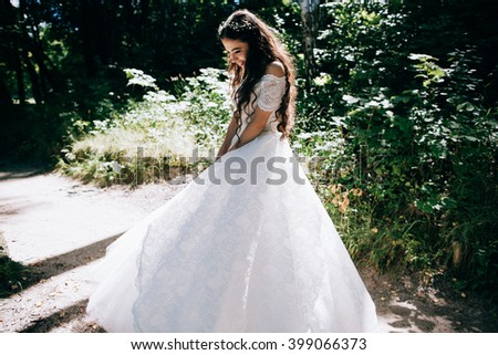 Happy Beautiful sensual bride with rustic wedding hairstyle in the forest. Outdoor portrait of young gorgeous bride. Wedding. Smile - stock photo
