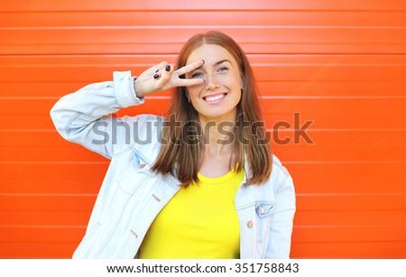 Happy beautiful smiling woman having fun over colorful orange background - stock photo