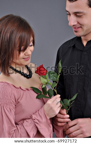 happy beautiful teenage couple, a boy giving a rose to his girlfriend - stock photo