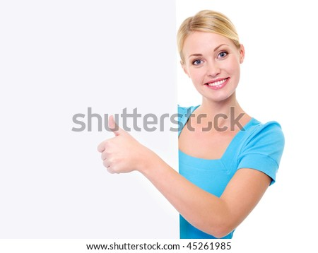 Happy beautiful toothy smiling woman looks out from of the  banner and showing thumbs-up - stock photo