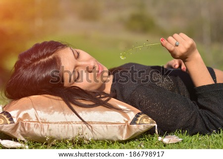 Happy beautiful woman blowing dandelion while laying on pillow outdoor, teen girl enjoying nature, summer vacation and holidays, young pretty female holding flower, wish concept  - stock photo