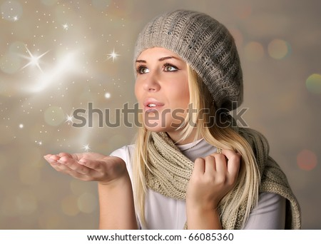 Happy beautiful woman blowing snowflakes in winter season - stock photo