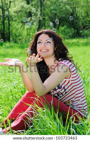 Happy beautiful woman catches soap bubbles on meadow - stock photo