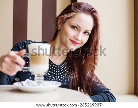 Happy beautiful woman drinking coffee in a cafe - stock photo