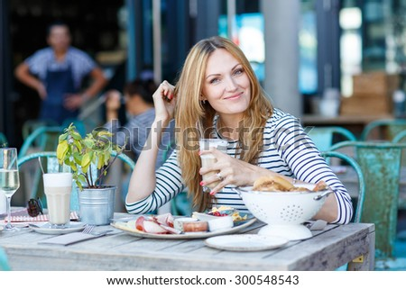 Happy beautiful woman drinking coffee with milk and having healthy breakfast in outdoor cafe in summer city in Europe. - stock photo