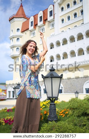 Happy beautiful woman in ethnic dress near the medieval castle, focus on girl  - stock photo