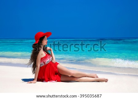 Happy beautiful woman in red hat enjoying sunny day lying on exotic beach in summer by tropical blue water. Attractive woman in red dress resting, outdoor portrait. Bliss freedom concept. Travel. - stock photo
