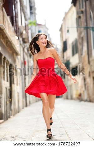 Happy beautiful woman in red summer dress walking and running joyful and cheerful smiling in Venice, Italy. Pretty sexy fashion model girl in her 20s. Mixed race Asian Caucasian female model outside. - stock photo