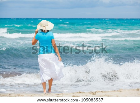 Happy beautiful woman in the beach hat looking at the sea - stock photo