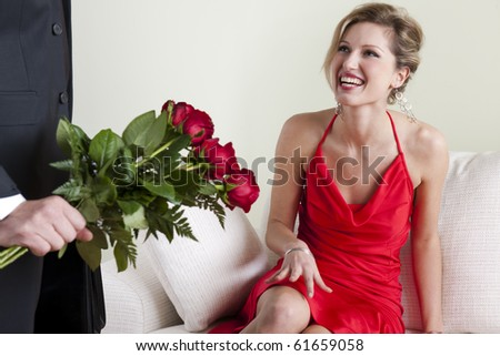 Happy beautiful woman receiving red roses on Valentine's Day, Birthday or Wedding Anniversary - stock photo