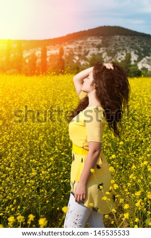 Happy beautiful woman resting in blossom spring garden with field flowers on nature looking happy smiling outdoors. Brunette girl on grass in park enjoying life. Indian woman with glossy healthy hair - stock photo