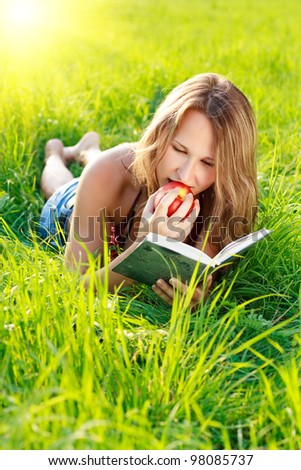 Happy beautiful woman with an apple in hand lying on the green grass and reading a book a sunny day against a background of green nature - stock photo