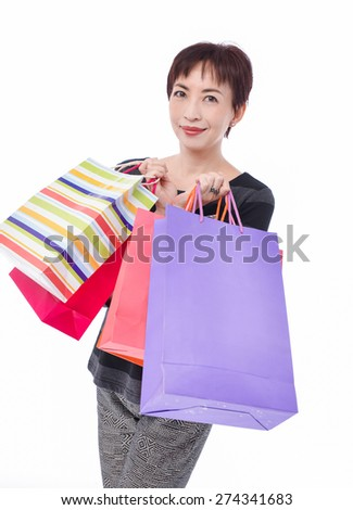 happy beautiful woman with shopping bags posing in studio - stock photo