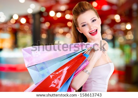 Happy beautiful woman with shopping bags stands at shop - stock photo