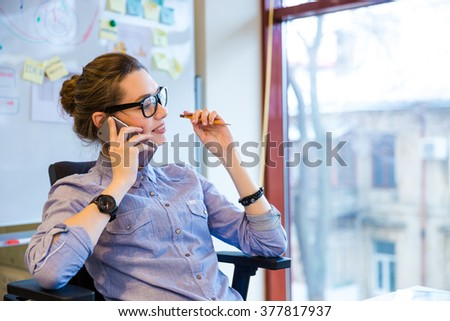 Happy beautiful young business woman in glasses sitting and talking on cell phone in office - stock photo