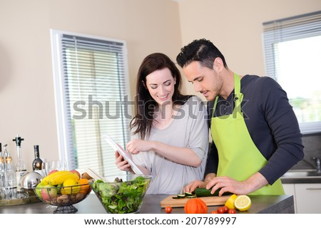 happy beautiful young couple preparing organic vegetables salad for lunch together in kitchen for summer party - stock photo