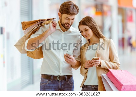 Happy beautiful young couple smiling, holding shopping bags and using smart phones while standing in mall - stock photo