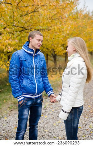 Happy beautiful young couple walking outdoors on cold autumn day - stock photo