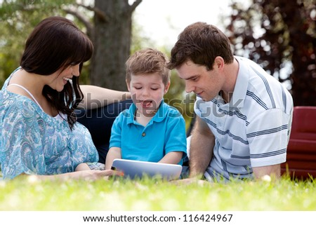 Happy beautiful young family in park with digital tablet - stock photo