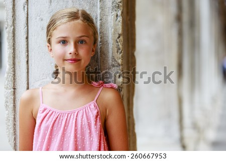 Happy beautiful young girl in summer dress posing joyful and cheerful smiling in Venice, Italy. - stock photo