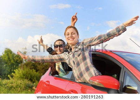 Happy beautiful young girls in a red car in the sunset. Travel concept. - stock photo