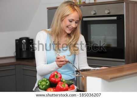 Happy beautiful young housewife cooking dinner standing over a pot on the stove stirring the ingredients with a bowl of fresh sweet peppers alongside - stock photo