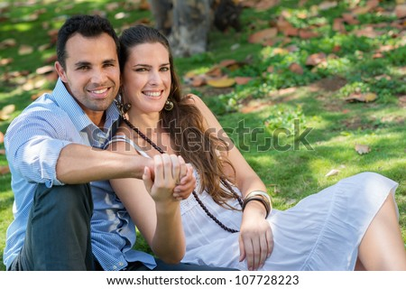 Happy beautiful young man and woman in love, lying on grass in park and relaxing - stock photo