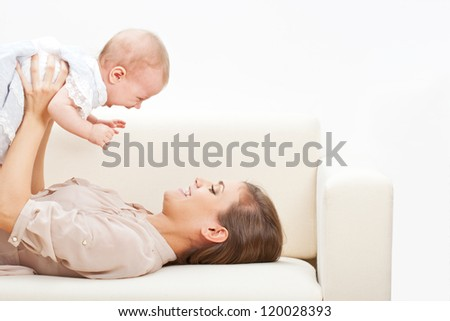 happy beautiful young mother and baby laying on sofa - stock photo