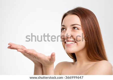 Happy beautiful young woman holding copyspace on palms and ready to catch something over white background - stock photo