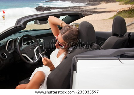 Happy beautiful young woman sitting in a sports car and using mobile smart phone on beautiful summer day on the beach. - stock photo