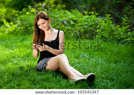 Happy beautiful young woman sitting on grass using smartphone - stock photo